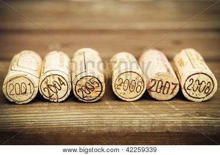 Dated wine bottle corks on the wooden background. Close up poster
