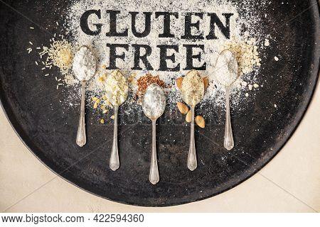 Gluten free written in flour on vintage baking sheet and spoons of various gluten free flour (almond, buckwheat, rice, corn, oatmeal), gluten free baking concept