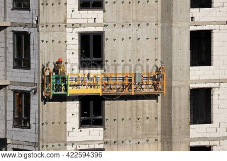 Worker Standing On Lifting Platform Near The Wall Of Unfinished House. Construction Works, Residenti