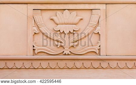 Beautiful embossed sculpture or carved decorative design on the stone wall. Ornamental Lotus graphic engraved on sand stone.