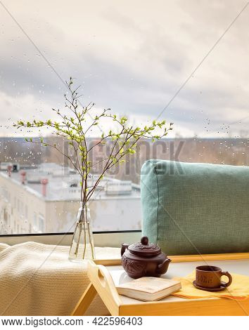 Spring Twigs In The Bottle On The Table With A Plaid, Pillow, Book, Teapot And A Cup With A Rainy Ci