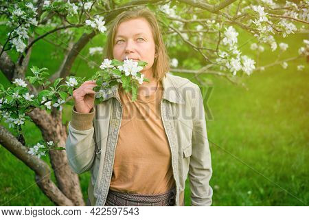 Portrait Of Smiling Adult Woman 40 Years Old Walking In Spring Apple Orchard