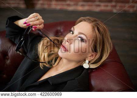Portrait of an attractive middle-aged woman with enlarged full lips, evening makeup and bright manicure lying on a leather sofa. Cosmetology, plastic surgery, rejuvenation.