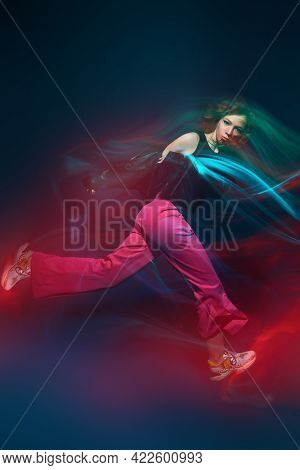 Contemporary dances. Professional hip hop dancer girl dancing at studio in neon light. Motion.