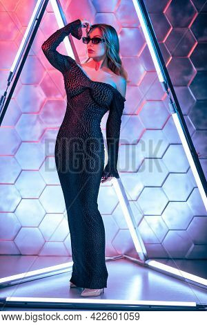 High fashion shot. A glamorous middle-aged woman in a form-fitting evening dress and black sunglasses under neon lights. Full length portrait. Luxury lifestyle.