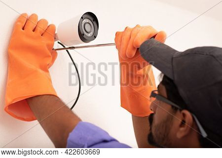 Shoulder Shot Of Electric Technician Man Setup Cctv Camera Security System On Wall - Electrician Ins