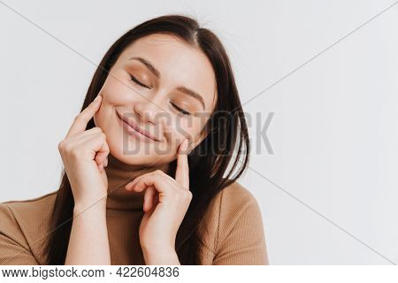 Happy young brunette white woman in casual clothes standing over white background, eyes shut