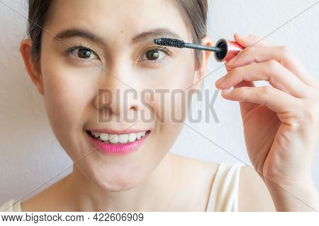 Close-up Of Young Asian Woman Applying Black Mascara On Her Eyelashes With Makeup Brush. Mascara Is