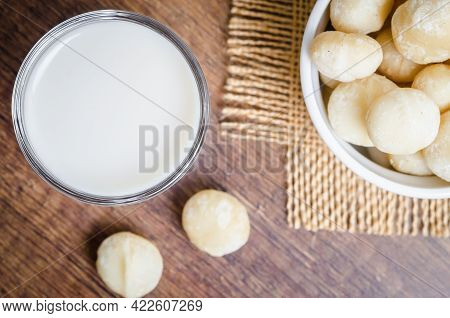 Macadamia Milk In A Glass And A Bowl Of Macadamia Nuts On A Wooden Background.
