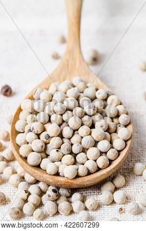 Dried White Peppercorn Seeds In Wooden Spoon.