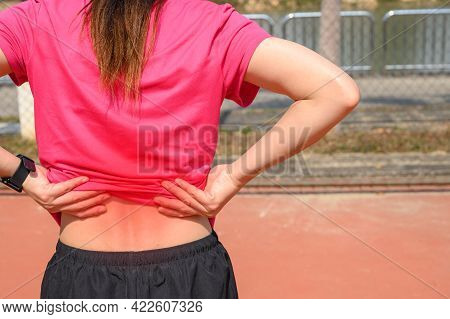 Back View Of Young Runner Woman Suffering From Lower Back Pain Or Sore Waist After Running Or Sport