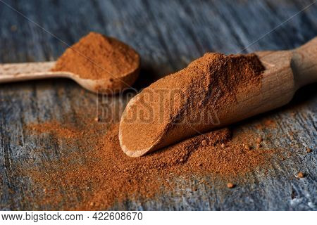 a wooden measuring scoop and a wooden spoon full of camu-camu powder on a gray rustic wooden table