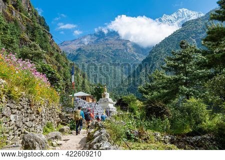 Group Of Tourist Walking In Local Sherpa Village In Sagarmatha National Park Of Nepal With View Of M