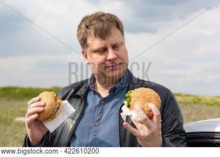 A Glutton With Two Burgers Decides Which One To Eat First.