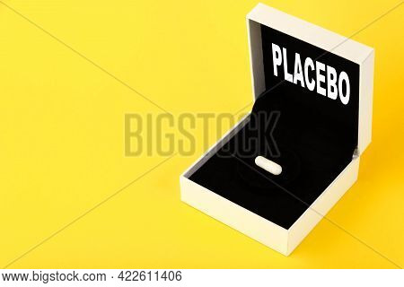 Placebo, The Text Is Written On A Gift Box, A Gift With One White Capsule, On A Yellow Background. C