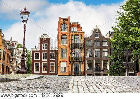 Traditional Dutch houses in the historic city of Amsterdam. Famous and popular tourist destination in the capital city of the Netherlands. A row of unique townhouse with cobbled street.