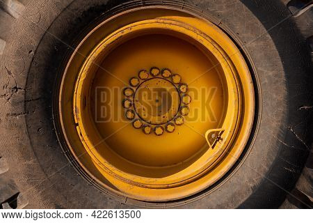 Close-up Of A Large Yellow Wheel Rim With An Old Tire And Large Bolts. Loader Wheel. Tire Service.