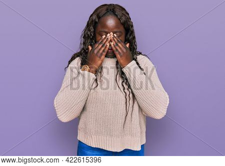Young african woman wearing wool winter sweater rubbing eyes for fatigue and headache, sleepy and tired expression. vision problem