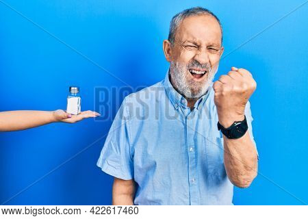 Handsome senior man with beard being offering salt annoyed and frustrated shouting with anger, yelling crazy with anger and hand raised
