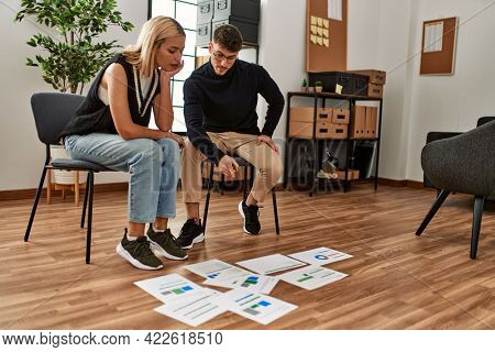 Two business workers looking paperworks on the floor working at the office.