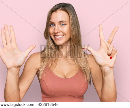 Beautiful caucasian woman wearing casual clothes showing and pointing up with fingers number eight while smiling confident and happy.