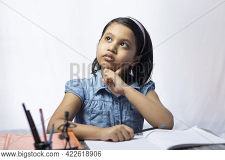 A Pretty Indian Girl Child Thinking And Looking Upward While Studying