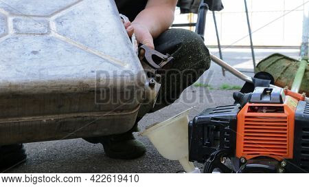 The Lawnmower Pours Gasoline From A Metal Can Into The Mower Container Through A Plastic Funnel, Ref