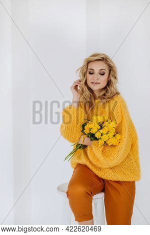 Happy Young Blonde Woman With A Bouquet Of Yellow Roses In A Voluminous Sweater Posing On A White Ba