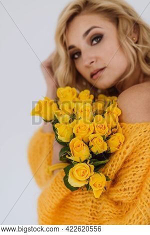 Portrait Of A Beautiful Young Blonde Woman With A Bouquet Of Yellow Roses In A Voluminous Sweater On