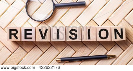 Wooden Cubes With The Word Revision Stand On A Wooden Background Between A Magnifying Glass And A Pe