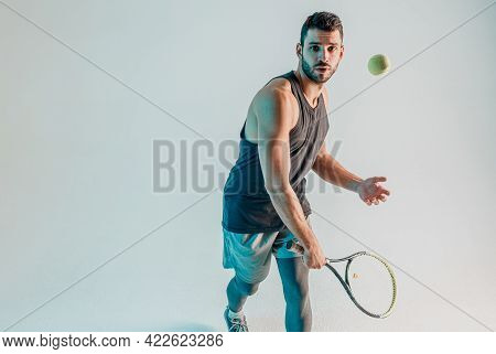 Sportsman Hit Tennis Ball With Racquet In Studio