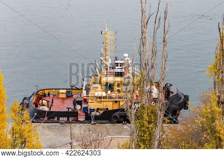 The Tug Is Moored At The Pier. A Brand New Small Tug Is Moored Parallel Behind The Trees.