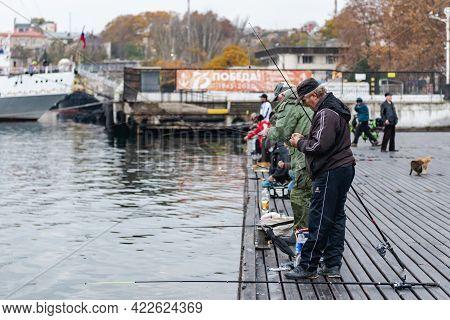 Sevastopol. Crimea. December 2021. Fishermen In Sevastopol On The Pier. On The Wooden Pier, Many Fis
