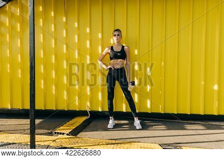 Young attractive athlete girl after intense training outdoors, resting near the yellow urban wall. Fitness sport girl resting after intensive run