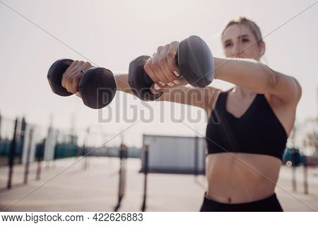 Woman in fitness wear exercising with dumbbells in outdoor sports ground.