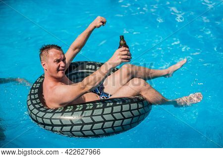 Happy Young Man Relaxing And Drink Beer In Swimming Pool