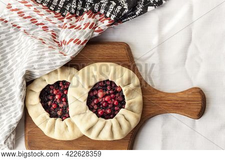 Homemade Sweet Galette With Elderberries And Cowberries On A Wooden Board. Flat Lay, Top View