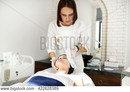 Doctor Aesthetician Performing Beauty Procedure On Woman Face, Removing The Rest Of Alginate Mask Us