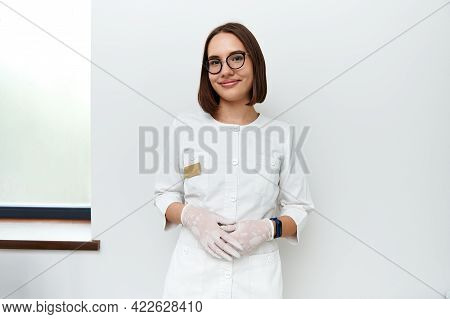 Confident Portrait Of A Young Female Doctor In White Medical Lab Coat And Protective Gloves Looking