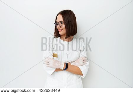 Beautiful Female Doctor Looking Away While Posing On Camera Over White Background With Copy Space