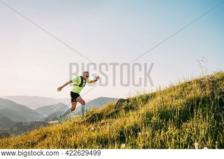 Middle-aged Mountain Trail Runner Man Dressed Bright T-shirt With A Backpack In Sports Sunglasses En