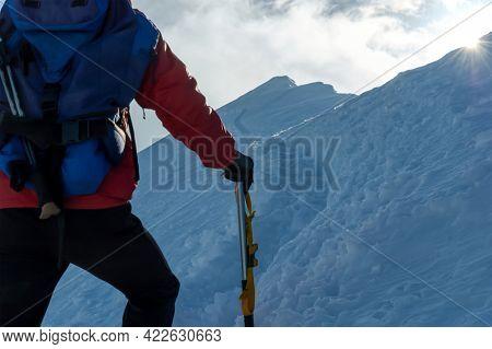 Mountaineer climbing a snowy ridge at sunrise. Swiss Alps, Europe.