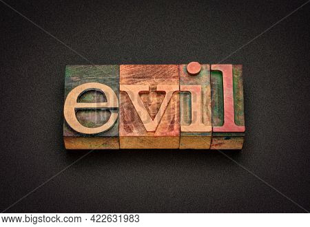 evil word abstract in vintage letterpress wood type, religious and ethical concept