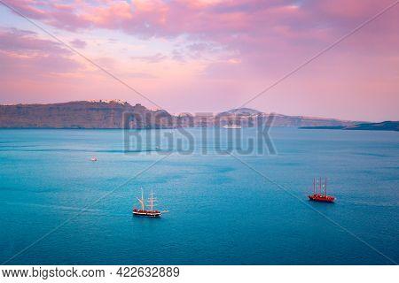 Tourist schooner vessel ships boat in Aegean sea near Santorini island with tourists going to sunset viewpoint. Santorini, Greece