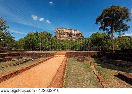 Famous tourist landmark of Sri Lanka - ancient Sigiriya rock (Lion rock) with palace fortress ruins on top in Sigiriya, Sri Lanka with foot path road. UNESCO World Heritage Site