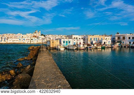 Picturesque view of Naousa town in famous tourist attraction Paros island, Greece with traditional whitewashed houses and moored fishing boats on sunset