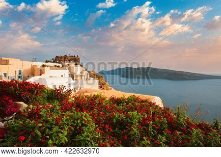 Tourist crowd gathered on sunset viewpoint to watch the sunset above Aegean sea in Oia Village, Santorini island, Greece