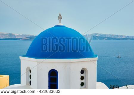 Famous view from viewpoint of Santorini Oia village with blue dome of whitewashed greek orthodox Christian church of traditional greek architecture. Oia town, Santorini island, Greece