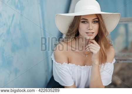 A Beautiful Young Woman With Long Blond Hair, Gray Eyes, Clean Skin And Pink Lips In A Straw Hat Loo