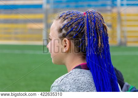 Ukraine, Khmelnytsky. June 2021. Young Girl With Fashionable Hairstyle With Braided Blue Ribbons In